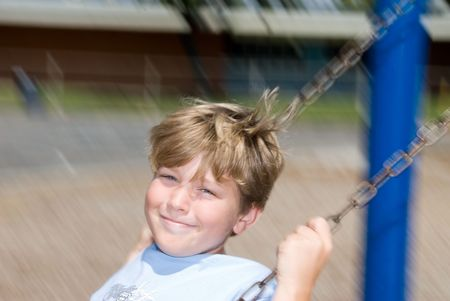 Kid playing on a schools swingset during recess photo