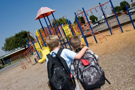 ni�os saliendo de la escuela: Contemplar dos hermanos jugando en el patio de recreo de la escuela antes de la escuela  Foto de archivo