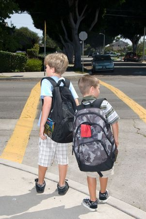to ensure: Two brothers watch for traffic at a crosswalk to ensure their safety Stock Photo