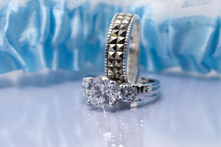 inset: Diamond ring and wedding band set against a blue garter belt on a reflective surface