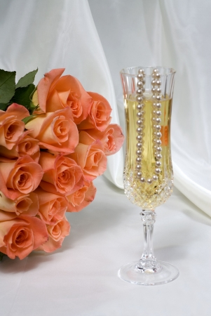 Wedding toast crystal glasses with champaign and pearls with peach roses shows the theme of a couples wedding Stock Photo