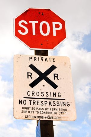 trespass: A stopsign together with a railroad warning communicates to passerbys that it is unsafe and illegal to trespass on private property.