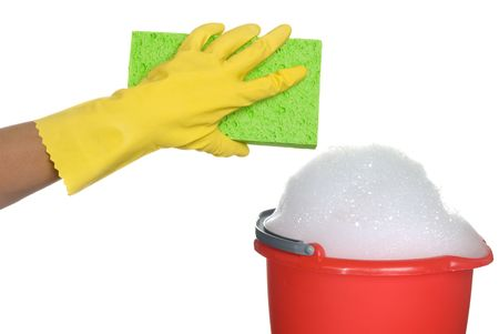 Worker protecting hand from detergents as they use a cleaning sponge and a soapy bucket of detergent. photo