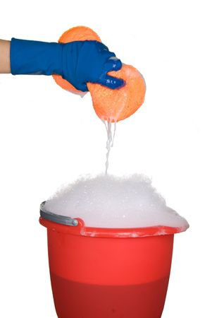 Worker protecting hand from detergents as they use a cleaning sponge and soapy water from a bucket.. photo