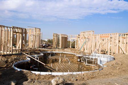 이미지는 수영장 공사와 함께 프레이밍 단계에서 건설중인 주택을 보여줍니다. 루핑 광고 및 기타 주택 건설 홍보 추론에 이상적입니다. 스톡 콘텐츠 - 2354124