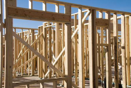 inferences: Image shows a home under construction at the framing phase.  Ideal for new construction advertising and other home construction promotional inferences Stock Photo
