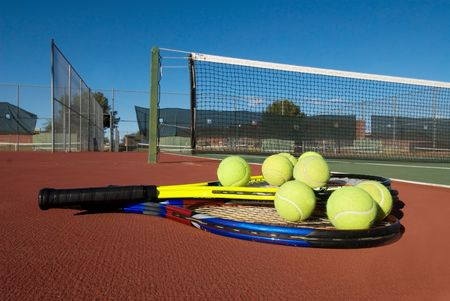 An image depicting the concept of tennis, including the court, racquets, balls and blue outdoors. Stok Fotoğraf