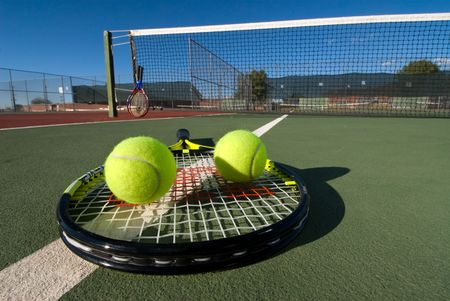 An image depicting the concept of tennis, including the court, racquets, balls and blue outdoors. Stock Photo