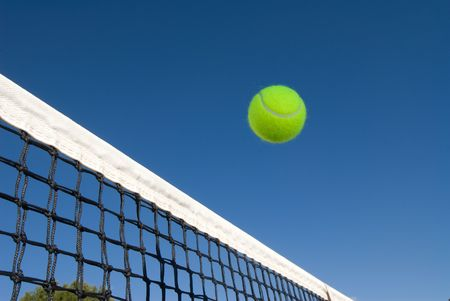 tennis clay: An image depicting the concept of tennis, including a ball gliding over the net in a blue outdoor setting