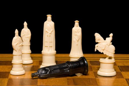 Chess set against a black background shows the king of the opposing side succumbing to defeat. Reklamní fotografie