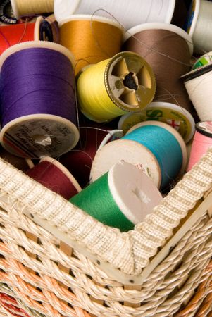 basket embroidery: The concept of sewing and embroidery is highlighted by colorful spools of thread in a sewing basket Stock Photo