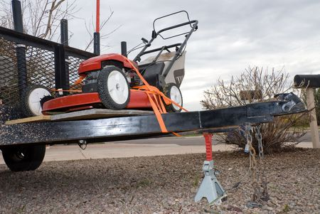 A lawn mower rests on a platform on the trailer of a gardners truck.