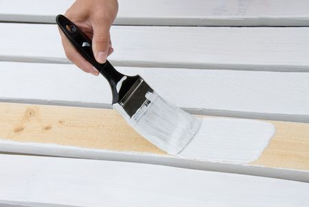 priming brush: A painter primes the wooden slats of a fence that is being constructed.