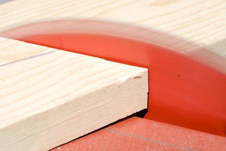 buzz saw: A table saw blade cuts a piece of pine