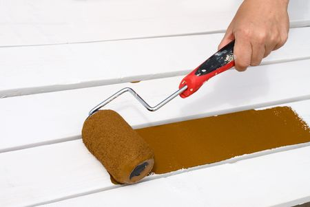priming brush: A painter rolls a brown paint layer onto newly primed wood.