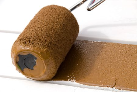 priming brush: A painter rolls brown paint on freshly primed wood