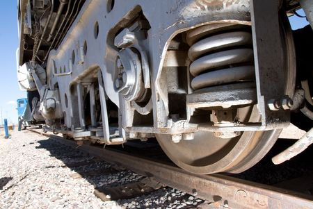 A train track and train wheel give great perspective to the size and power of railway transportation. Banco de Imagens