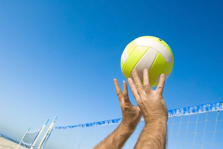 beach volleyball: A volleyball player lobs a ball during a game at the beach.
