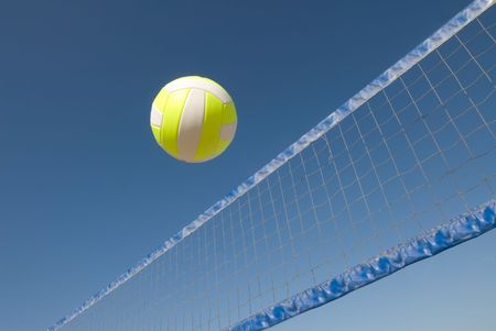 net: A volleyball player lobs a ball during a game at the beach.