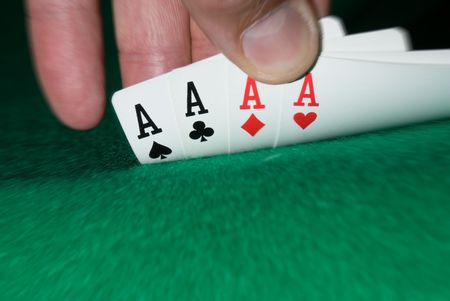 A gambler peeks to see what his cards are.  A nice four aces reveals lots of luck and a good player.