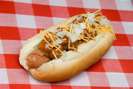 dog summer: A scrumptious barbecued chili dog with onions, mustard and cheese rests on a picnic table waiting to be consumed.