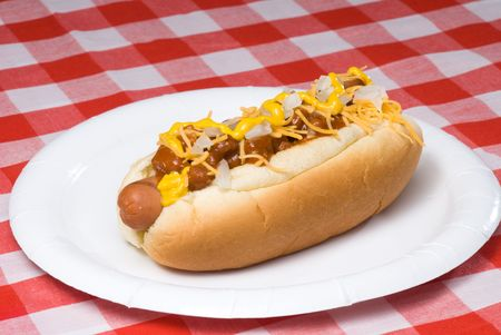 A scrumptious barbecued chili dog with onions, mustard and cheese rests on a picnic table waiting to be consumed.