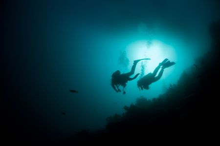 skin diving: Two scuba divers hoover in open ocean against the bright sun Stock Photo