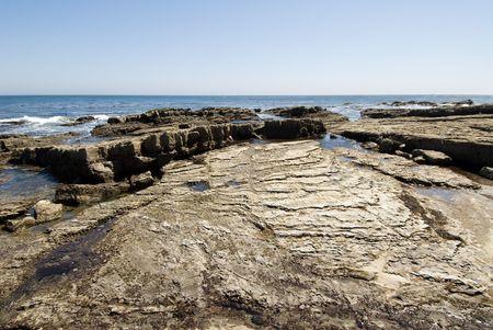 barnacles: Una vista di un Tidepool durante la bassa marea espone una barriera netta coperta di conchiglie