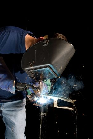 attaching: A welder fabricates a tool by attaching two pieces of metal. Stock Photo