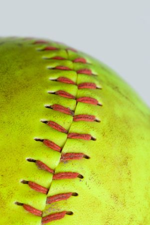 stitching: An old green softball shows its colorful red stitching.