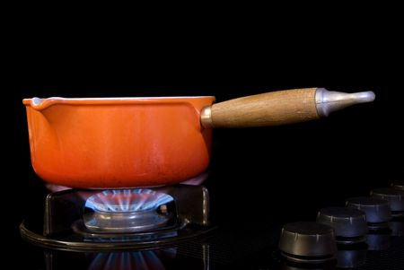 boiling: A boiling pot of water on a black stove with gas flame.