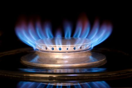 A blue flame on a gas range isolated against a black marble splash. Stock Photo