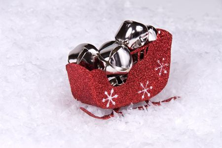 A red sleigh of silver Christmas bells waits for Santa.