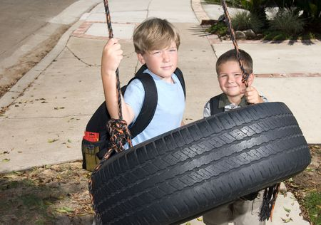 Two kids play on a tire swing after school. Stock Photo