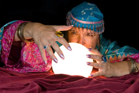 A gypsy fortune teller brings her crystal ball to life to read the future. Stock Photo