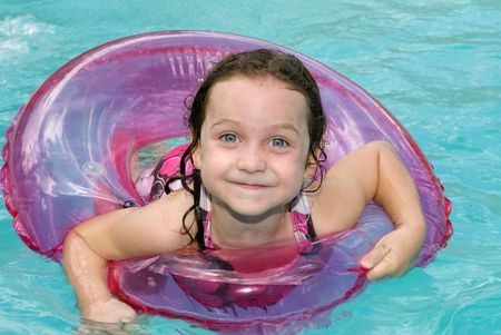 A little girl floats in her safety ring while cooling off during a hot summer day. Stock Photo - 3820659