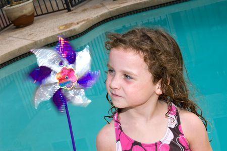 intrigued: A young girl is intrigued by a spinning pin wheel toy after a day of swimming