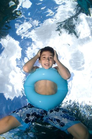 A boy floats on his blue floatation ring looking down underwater while I rest on below him with my underwater camera system and shoot straight up to a blue sky full of clouds and palm leaves. photo