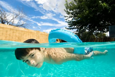 A boy floats on his blue floatation ring looking down underwater while I rest on below him with my underwater camera system and shoot a split level image of him swimming.
