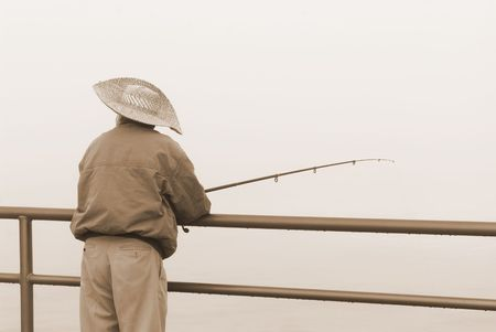 A fisherman relaxes during a cold, foggy morning.  Stock Photo - 3820106