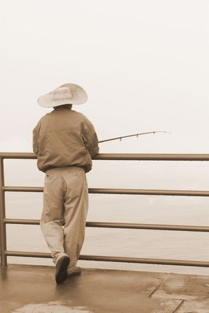 A fisherman relaxes during a cold, foggy morning.  Stock Photo - 3820275