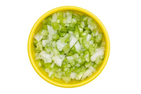 A bowl of chopped onions and bell pepper isolated on white.
