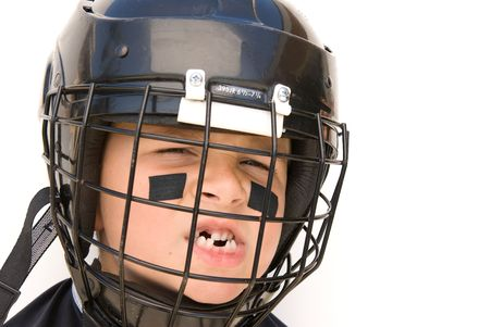 squint: A young boy shows off his missing teeth while in his hockey gear.