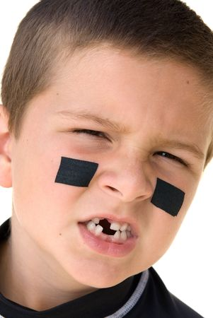 A young boy getting reaqdy to play hockey snarls at the camera to show off his missing teeth.