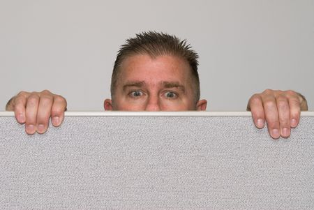 office cubicle: A male office worker peers over a cubicle because he is nosey. Stock Photo