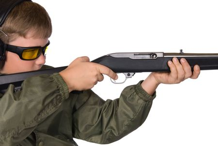 hearing protection: A boy aims his rifle.  He is properly dressed wearing eye and hearing protection. Stock Photo