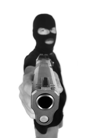 A robber with hidden face points his gun in a robbery attempt.   Stock Photo