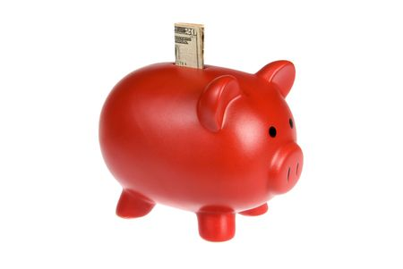 A red piggy bank with a twenty dollar bill isolated on a white background.