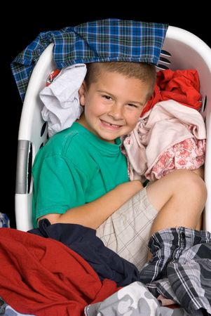 A young boy curls up in a warm clothing basket full of freshly dried clothes. Stock Photo