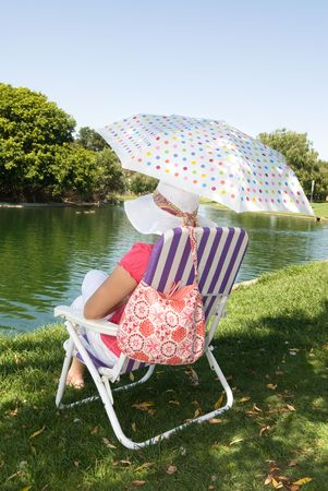 A woman sits near the edge of a lake while relaxing on a Sunday morning. photo